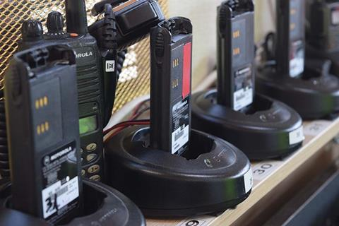 Several two way radios sitting on a shelf